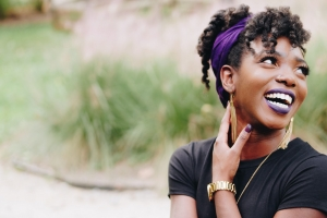 African American woman with dark brown skin smiling and looking into the distance.
