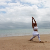 Image of a Black woman in Warrior yoga pose on the beach. The sky around her is slimly dark and stormy. This image depicts her thriving through the storm.
